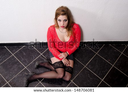 Young woman victim of human trafficking sitting on the floor. - stock photo