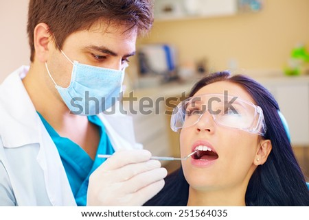 young woman visiting dentist doctor in clinic - stock photo