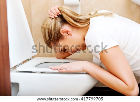 Young woman voimiting in the bathroom - stock photo