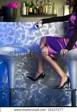 young woman waiting alone in bar and holding mobile phone - stock photo