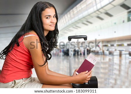 Young woman waiting at an airport, holding tickets - stock photo