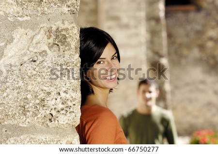 young woman waiting for her boyfriend standing near a wall - stock photo