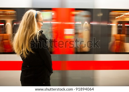 Young woman waiting for incoming train/subway - stock photo