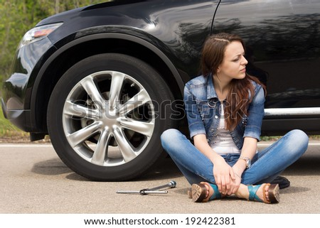 Young woman waiting for roadside assistance for her car sitting cross legged in the road looking expectantly down the road with the wheel spanner lying alongside her - stock photo