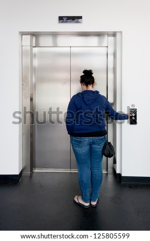 Young woman waiting in bright hallway and calling the elevator