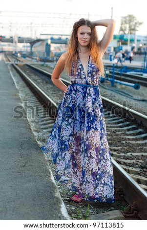 Young woman waiting train on the platform of railway station - stock photo