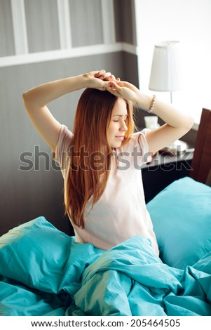Young woman waking up and stretching in her bed - stock photo