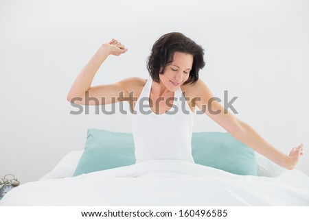 Young woman waking up in bed and stretching her arms - stock photo