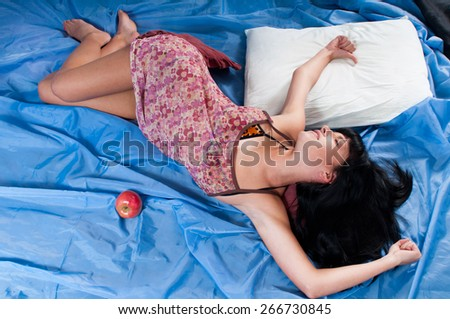 Young woman waking up in the morning with red apple in bed