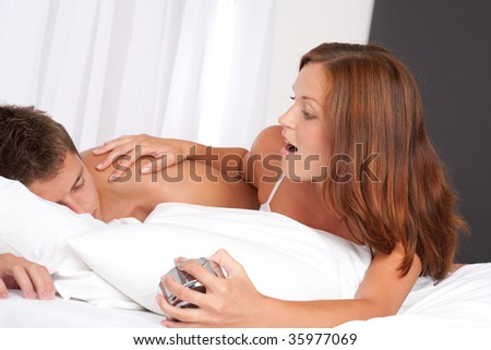 Young woman waking up man holding alarm clock