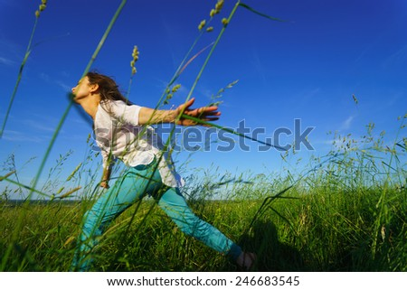 Young woman walk on green field - stock photo