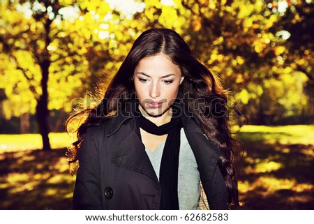 young woman walking accros the autumn park - stock photo