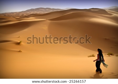 Young woman walking alone in the desert. Moroccan background - stock photo