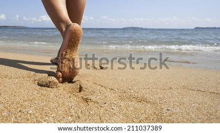 Young woman walking alone on sand beach. Closeup detail of female feet and golden sand. - stock photo