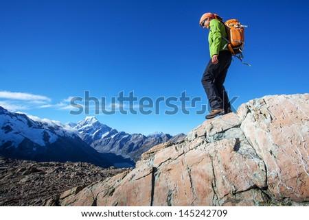Young woman walking along mountain ridge - stock photo