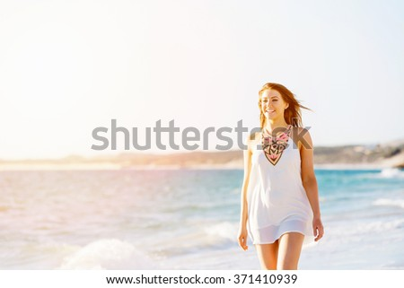 Young woman walking along the beach - stock photo
