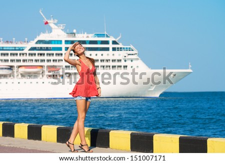 Young woman walking along the quay, the ship sailing by - stock photo