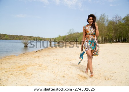 young woman walking along the river bank