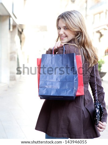 Young woman walking and shopping in the city, turning to smile at camera while carrying paper bags over her shoulder, joyful and smiling. - stock photo