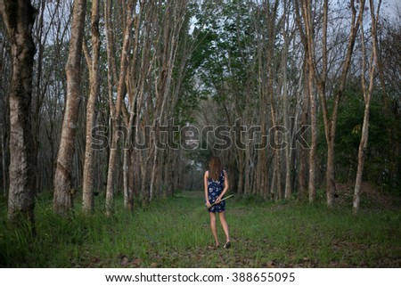Young woman walking away alone on a forest path  , hipster ,photo retouching  - stock photo