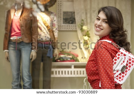 Young woman walking by a shop window. - stock photo
