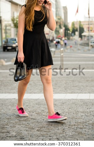 Young woman  walking down street in sneakers and high heels shoes holding in hands - stock photo