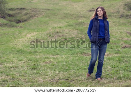 Young woman walking in a field.