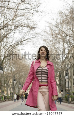 Young woman walking in a pedestrian street. - stock photo