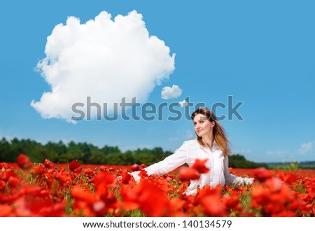Young woman walking in a poppy field looking to the clouds thought bubble in the blue sky - stock photo
