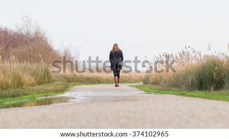 Young woman walking in a typical dutch landscape, selective focus