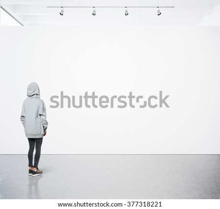 Young woman walking in modern gallery and looking at the blank canvas. Square - stock photo