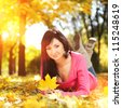 Young woman walking in the autumn park. Beauty nature scene with colorful foliage background, yellow trees and leaves at fall season. Autumn outdoor lifestyle. Happy smiling woman relax on fall leaves - stock photo