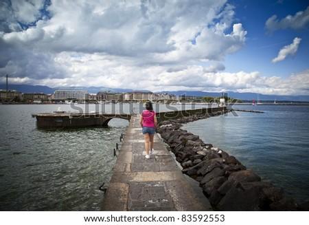 Young woman walking in the Jet d'Eau dock in Geneva - stock photo