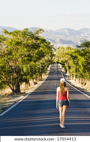 Young woman walking in the middle of the road. - stock photo