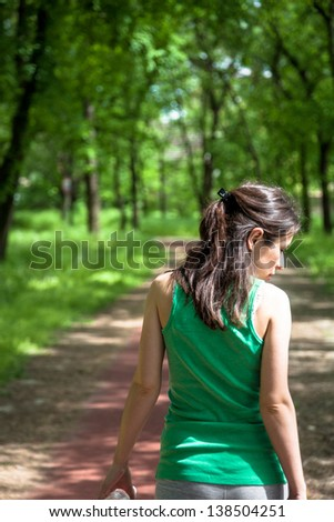 Young woman walking in the park - stock photo
