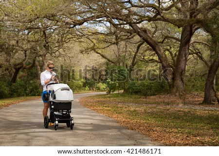 Young woman walking in the park with baby stroller. Happy mother with child in the carriage. Girl with a pram outdoors in the big park. - stock photo
