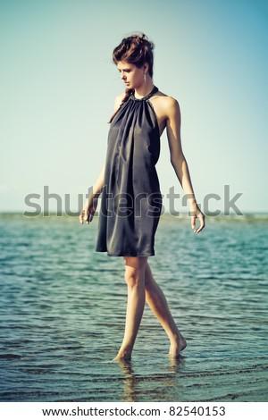 Young woman walking in water wearing purple dress - stock photo