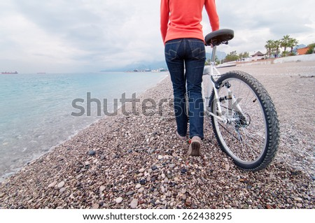 young woman walking near the sea with bicycle against sky background. Back view. - stock photo