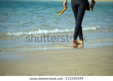 Young woman walking on a beach - stock photo