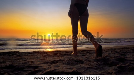 Young woman walking on a sandy beach splashed by ocean waves at sunset