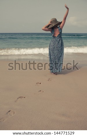 Young woman walking on a white sand beach