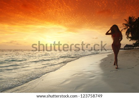 Young woman walking on beach under sunset light