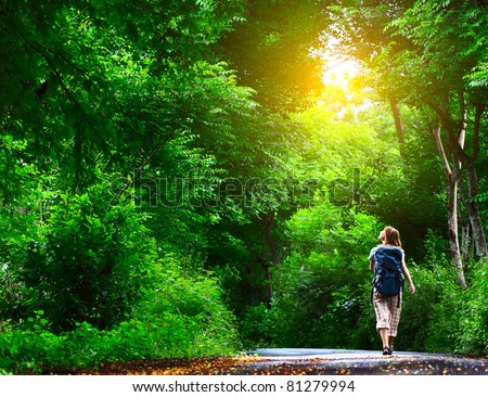 Young woman walking on green asphalt road in forest