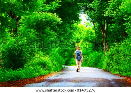 Young woman walking on green asphalt road in forest - stock photo