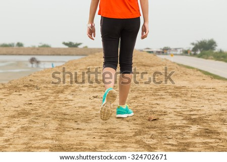young woman walking on mountain trail, closeup on leg