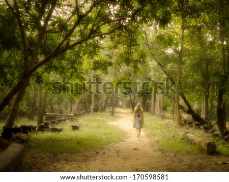 Young woman walking on mysterious path into an enchanted forest. - stock photo