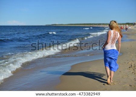 Young woman walking on sand beach