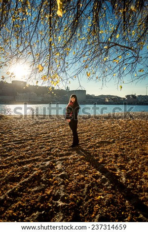 Young woman walking on sandy beach at cold autumn day - stock photo