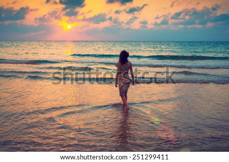 Young woman walking on seashore at sunset and looking at the sun - stock photo