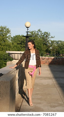 young woman walking on the balcony of the park - stock photo